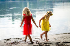 Blond girls in red dress and yellow dress at the river strand Royalty Free Stock Image