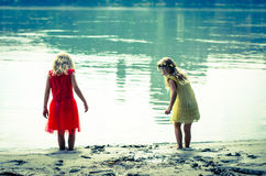 Blond girls in red dress and yellow dress at the river strand Stock Photo
