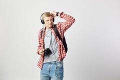 Blond grabb i hörlurar, med den svarta ryggsäcken på hans iklädda skuldra en vit t-skjorta, en röd rutig skjorta och en jeans arkivbilder