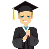Blond Graduation Boy. Happy blond student boy on graduation day holding diploma with both hands Royalty Free Stock Photography