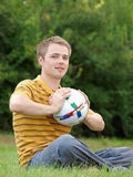 Blond on grass with ball Stock Images