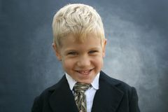 Blond grinning business boy. Adorable grinning blond boy wearing suit and tie centered on gradient gray background Stock Photography