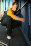 Blond guy by fence. Blond guy holding on to a fence on a street Royalty Free Stock Photography