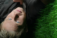 Blond guy on grass. Night photo of blond guy laying on grass Stock Photography