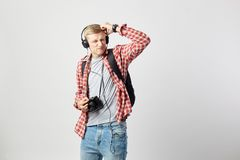 Blond guy in headphones, with black backpack on his shoulder dressed in a white t-shirt, red checkered shirt and jeans stock images