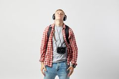 Blond guy in headphones, with black backpack on his shoulders dressed in a white t-shirt, red checkered shirt and jeans royalty free stock photo