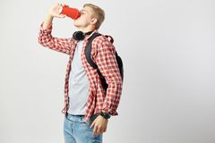 Blond guy in headphones, with black backpack on his shoulders dressed in a white t-shirt, red checkered shirt and jeans stock photo