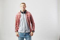 Blond guy with headphones on his neck dressed in a white t-shirt, red checkered shirt and jeans stands on the white royalty free stock photos