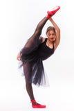 Blond härlig flicka i den svarta ballerinakjolklänningen som gör gymnastisk splittring arkivfoton