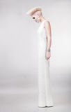 Blond härlig kvinna i klänning med den idérika frisyren arkivbild