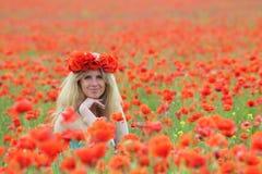 Blond-Haarfrau, die in den Mohnblumen sitzt Lizenzfreie Stockfotografie