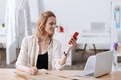 Blond-haarige Frau, die ihr Telefon betrachtet Lizenzfreie Stockfotografie