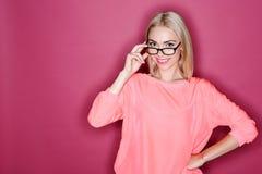 Blond-haarige Frau, die mit Gläsern aufwirft Stockbilder