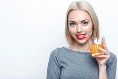 Blond-haarige Frau, die mit Glas Saft aufwirft Lizenzfreies Stockfoto