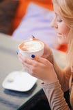 Blond-haarige Frau, die Tasse Kaffee hält Stockbild