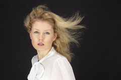 Blond-haarige Frau mit weißer Bluse in einem Sturm (Windmaschine) Stockbilder