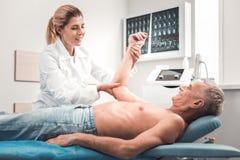 Blond-haariger junger Chiropraktor, der an der medizinischen Station arbeitet stockbilder