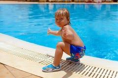 Blond-haariger Kinderjunge nahe dem Swimmingpool lizenzfreies stockbild