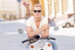 Blond-haariger Mann, der auf Roller sich lehnt Lizenzfreies Stockfoto