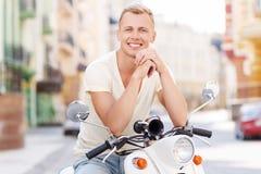 Blond-haariger Mann, der auf Roller sich lehnt Lizenzfreie Stockfotografie
