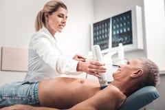 Blond-haariger Physiotherapeut, der Röntgen des Kastens tut stockbilder