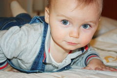 Blond hair blue eyes baby laying down on the bed closeup.  Stock Images