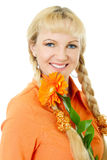 Blond hair and blue eyes girl in orange blouse holds flower african daisy Royalty Free Stock Photo
