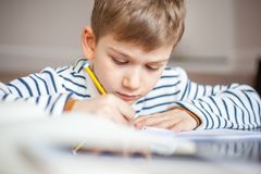 Adorable 7 years boy sitting at desk with book and writing royalty free stock photo