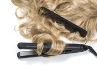 Blond hair with curling iron Stock Photos