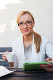 Blond hair girl sitting behind the table with cup of coffee and Stock Photos
