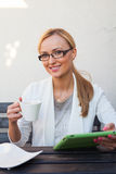 Blond hair girl sitting behind the table with cup of coffee and Royalty Free Stock Photo