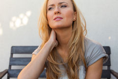 Blond hair girl sitting behind the table and suffering because o Stock Image