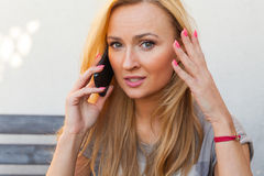 Blond hair girl sitting behind the table an talking by the phone Stock Photo