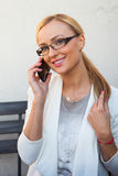 Blond hair girl sitting behind the table an talking by the phone Stock Image