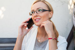 Blond hair girl sitting behind the table an talking by the phone Stock Photography