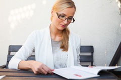 Blond hair girl in suit and glasses sitting on the bench and loo Royalty Free Stock Photo