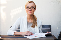 Blond hair girl in suit and glasses sitting on the bench and loo Stock Photography