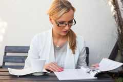 Blond hair girl in suit and glasses sitting on the bench and loo Royalty Free Stock Photos