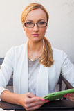 Blond hair girl in suit and glasses sitting on the bench with ta Stock Images