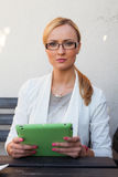 Blond hair girl in suit and glasses sitting on the bench with ta Royalty Free Stock Photo