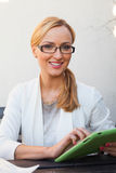Blond hair girl in suit and glasses sitting on the bench with ta Stock Image