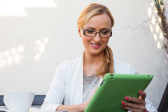 Blond hair girl in suit and glasses sitting on the bench with ta Royalty Free Stock Images