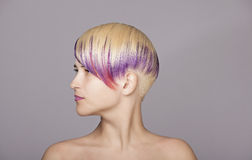 Blond hair girl with violet paint. Beautiful Woman Royalty Free Stock Photography