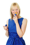 Blond hair girl wears blue dress and sniffs perfume Stock Images