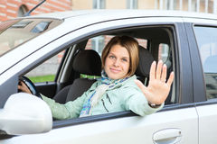 Blond hair greeting by hand from car window Royalty Free Stock Photography