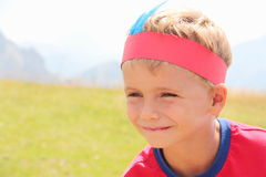 Blond hair kid playing indian outdoor.  Royalty Free Stock Image
