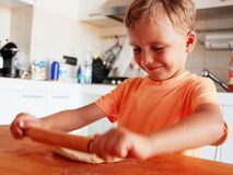 Blond hair little boy enjoys making pizza in the kitchen