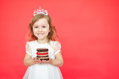 Blond hair little girl holding cake on red background Stock Image