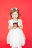 Blond hair little girl holding cake on red background Royalty Free Stock Images