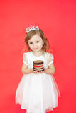 Blond hair little girl holding cake on red background Royalty Free Stock Image